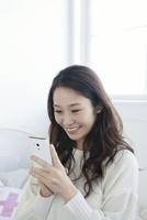 携帯でメールをする20代女性