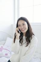 携帯で電話をする20代女性