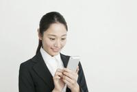 スマートフォンでメールをする20代ビジネスウーマン