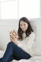 ベッドの上で本を開く20代女性