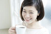 窓際でコーヒーを飲む20代女性