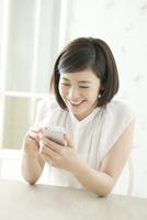 座りながら携帯を操作する20代女性