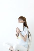 本を持ち見上げる若い女性