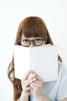 本で口元を隠す若い女性