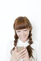 携帯電話を見る笑顔の20代女性