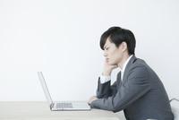 肘をつきながらノートパソコンを見るヤングビジネスマン