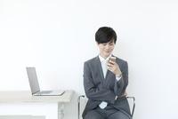 座りながら携帯電話を見るヤングビジネスマン
