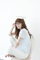 頭の上に本を置いてポーズする若い女性