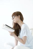 椅子に座り読書をする若い女性