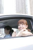 外の景色を楽しむ20代女性と運転する男性