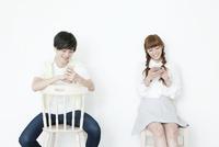 携帯電話を見る20代男性と女性
