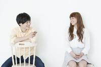 携帯電話をもちながら話す若い男性と女性