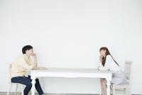 テーブルで向かい合う20代男性と女性