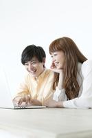 一緒にノートパソコンを見る20代カップル