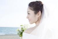 海辺に立つブーケを持つ花嫁
