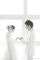 指輪をはめる新郎と笑顔の新婦 02299008134| 写真素材・ストックフォト・画像・イラスト素材|アマナイメージズ