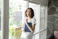 本をもって窓辺に立つ女性