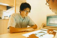 レントゲン写真を見る歯科医師と男性 日本人