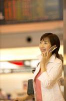 空港の出発ロビーで携帯電話をかける日本人女性 02308000014| 写真素材・ストックフォト・画像・イラスト素材|アマナイメージズ