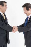 笑顔で握手するスーツの中年男性2人