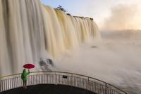 Visitor with red umbrella on viewing platform, Iguacu Falls,