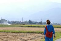 赤いバックをかけた女性と田んぼ 02332000034| 写真素材・ストックフォト・画像・イラスト素材|アマナイメージズ