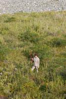 銃を持って草原に立つ女性 02332000039| 写真素材・ストックフォト・画像・イラスト素材|アマナイメージズ