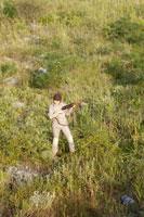 銃を持って草原に立つ女性