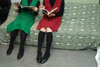 ソファに座り読書をする女性