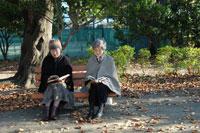 公園のベンチで読書をするシニア女性2人 02332000066| 写真素材・ストックフォト・画像・イラスト素材|アマナイメージズ