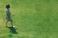 芝生の上を歩くチェックのワンピースを着た女の子 02332000195| 写真素材・ストックフォト・画像・イラスト素材|アマナイメージズ