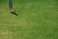 芝生の上を歩くチェックのワンピースを着た女の子