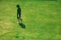 芝生の上を歩く紺色のワンピースを着た女の子