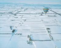 雪原の中を飛ぶ熱気球