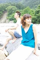 川原で腰掛ける日本人男性と女性