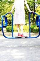 公園の遊具に乗る女性の足元