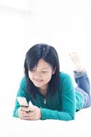 寝転んで携帯を見つめる10代女性