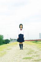 土手に立つ制服姿の日本人女性