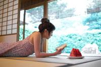 寝転んで本を読む日本人20代女性