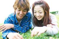 芝生の上に寝転ぶ日本人カップル