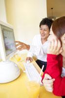 パソコンに向かう日本人20代カップル
