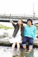 川辺に座る日本人20代カップル