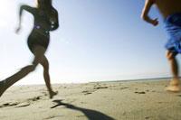 砂浜を走る男性と女性