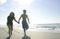 砂浜を歩く男性と女性