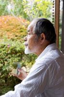 縁側でお茶を飲む日本人シニア男性