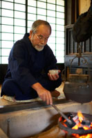 囲炉裏の前に座る日本人シニア男性