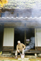 七輪でサンマを焼く日本人シニア男性