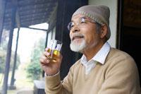 縁側でお酒を飲む日本人シニア男性