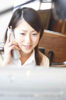 パソコンの前で電話をする女性