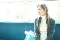 電車の中で音楽を聞く女性